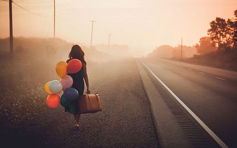 A woman walking on the side of a road, a suitcase in one hand, a handful of balloons in the other