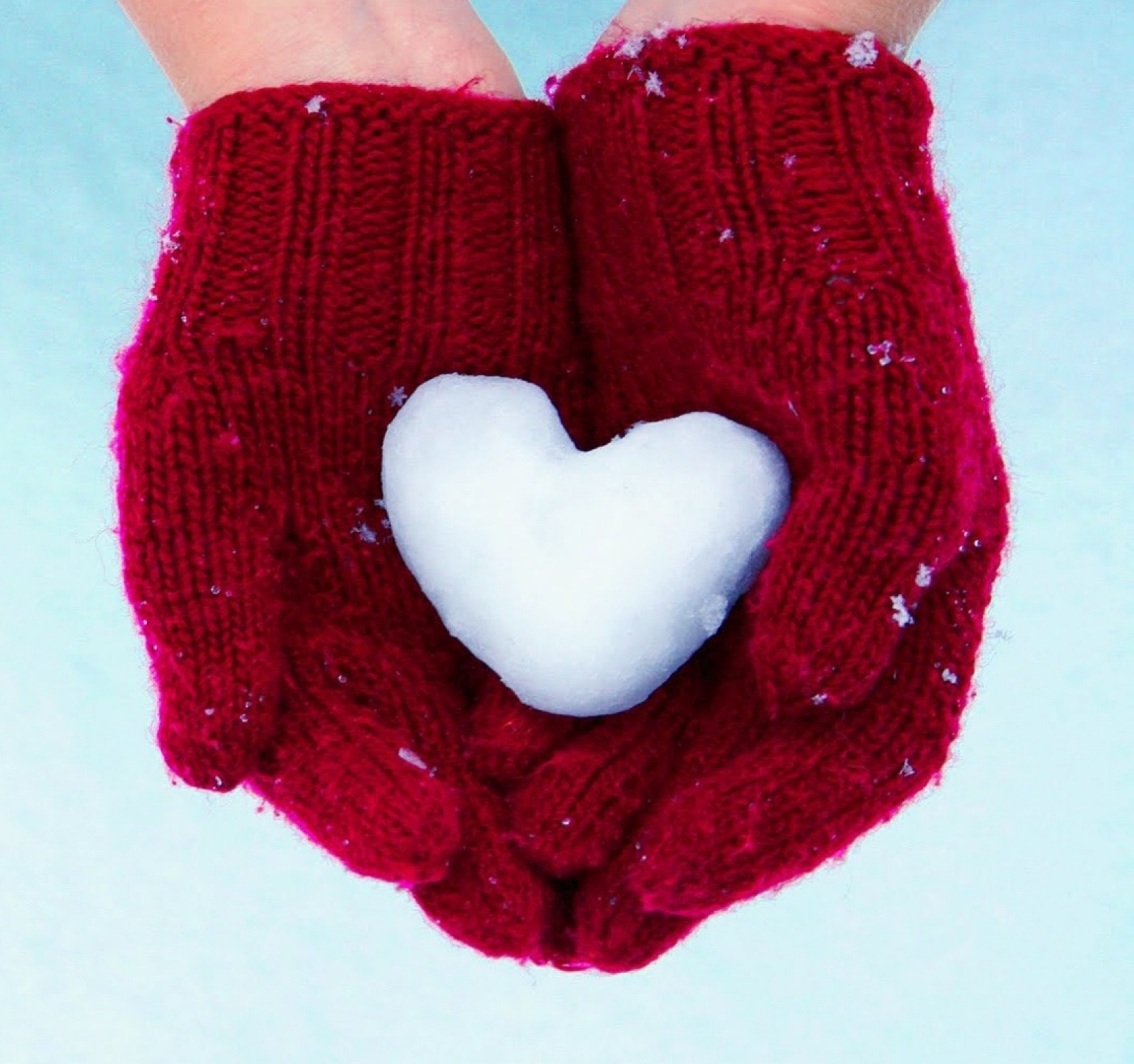 The hands of a woman wearing red mittens and holding a snow in the shape of a heart