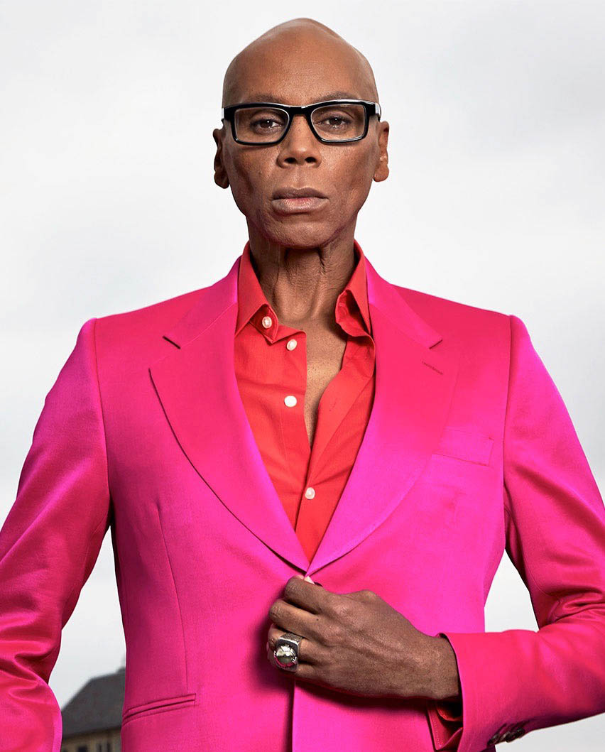 RuPaul not in drag, wearing a bright pink suit