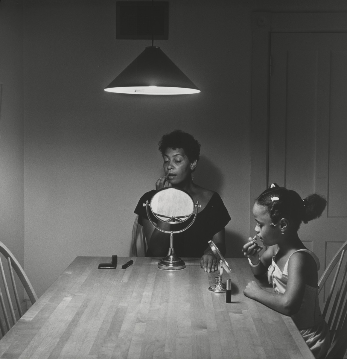 Carrie Mae Weems and a young girl, both at a kitchen table, putting on lipstick