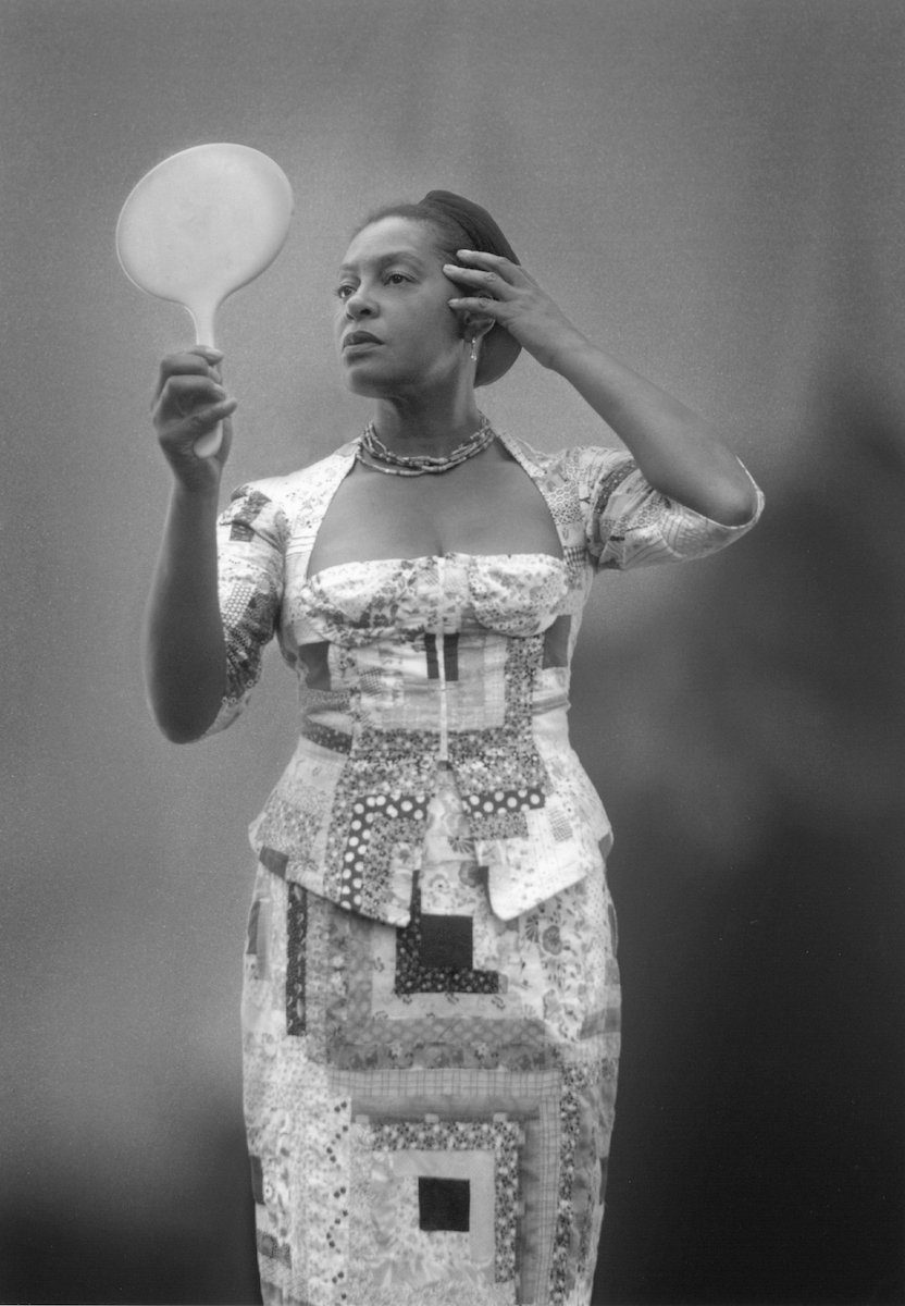 Self-portrait of Carrie Mae Weems holding up a mirror to her fac
