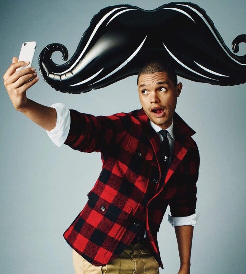 Trevor Noah taking a selfie while wearing a huge moustache balloon on his head