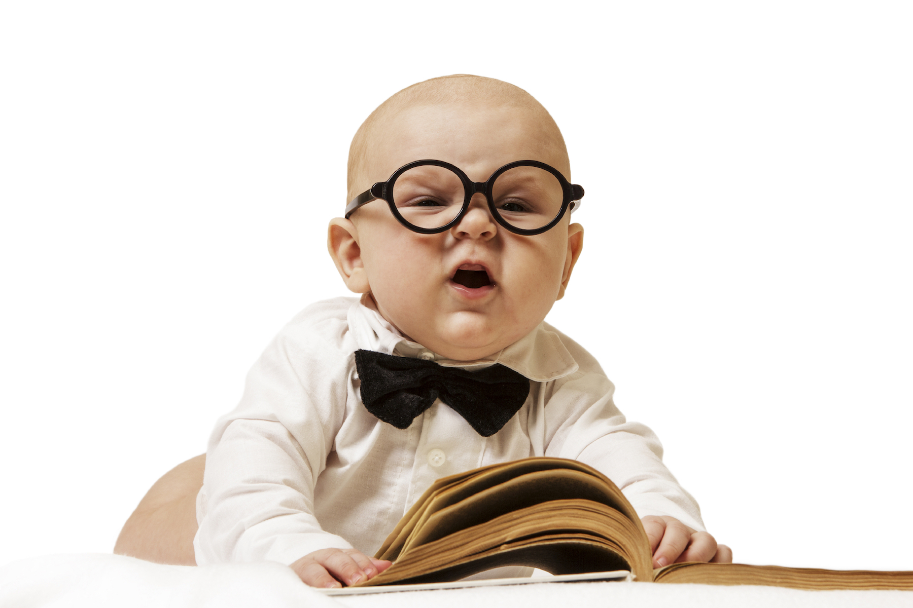 A baby wearing studious glasses and a bow tie while reading a big book
